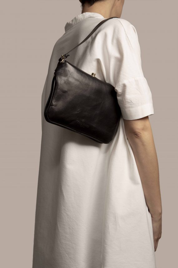 Handbag hanging by Petty Things model made of black vegetable dyed leather