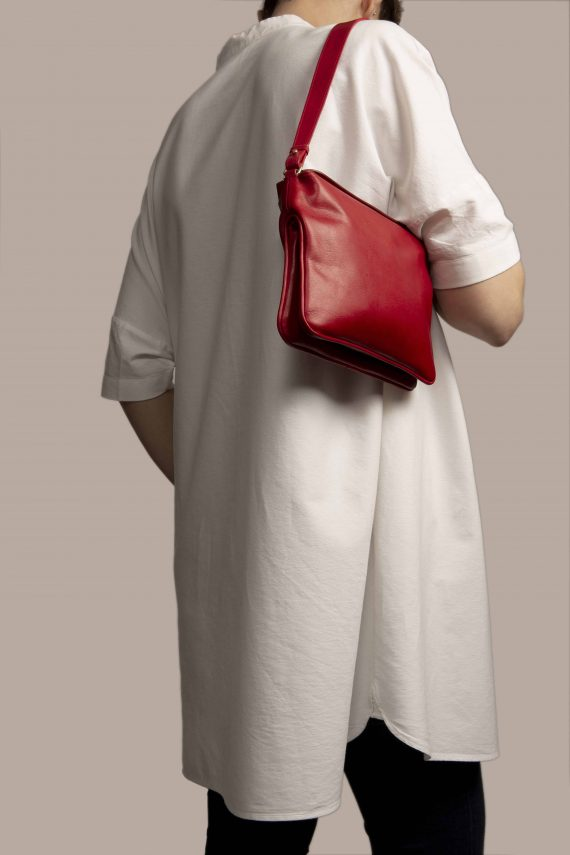 Handbag hanging from Petty Things model made of red vegetable dyed leather with vintage fabric barkcloth Fireworks