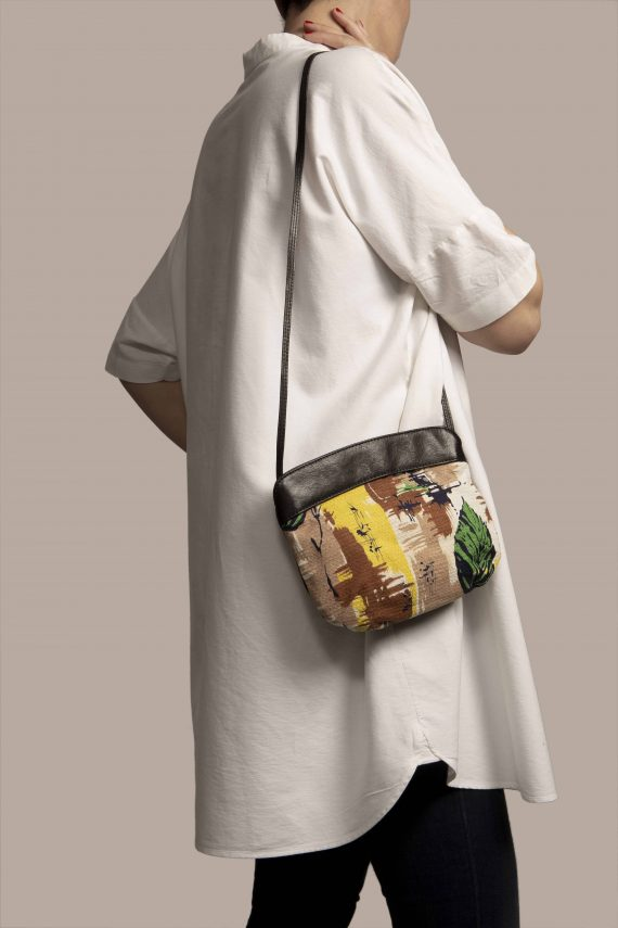 Crossbody bag hanging from human model shoulder made of black vegetable dyed leather with vintage fabric barkcloth Peter
