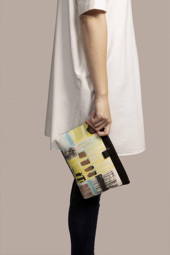 Vista lateral de modelo sujetando bolso de tela dePetty Things, hecho en cuero tinte vegetal color negro con tela vintage barkcloth Lane