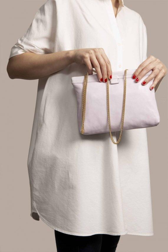Clutch de cuero color lila agarrado por mujer de Petty Things. Cuero con tinte vegetal