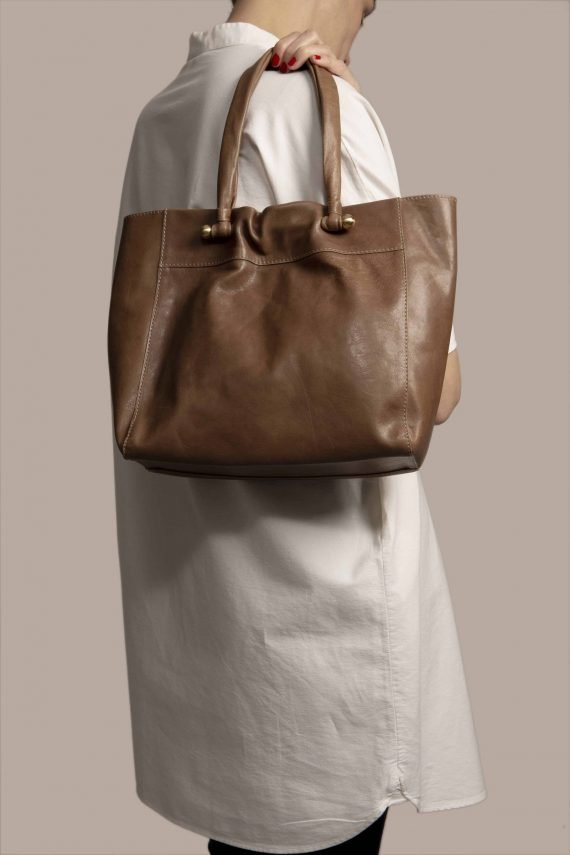 Tote bag hanging from human model shoulder, made in brown vegetable-dyed leather